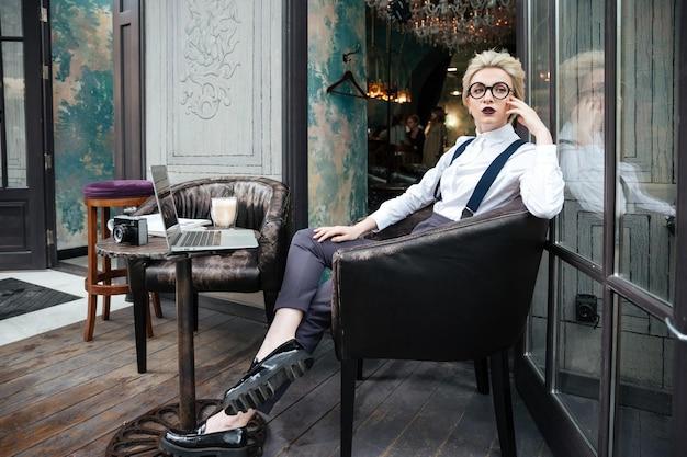 Rozważna młoda kobieta w okrągłych okularach siedzi w kawiarni na świeżym powietrzu i myśli