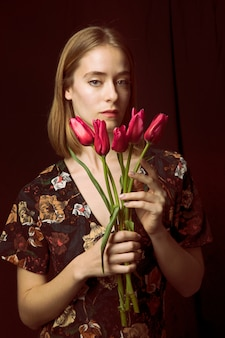Rozważna młoda kobieta z czerwonymi tulipanami
