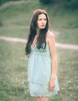 Rozważna młoda kobieta z długimi włosami stojąca na łące