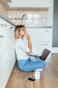 Rozważna młoda kobieta z filiżanką kawy i laptopem w lekkiej nowoczesnej kuchni w domu.