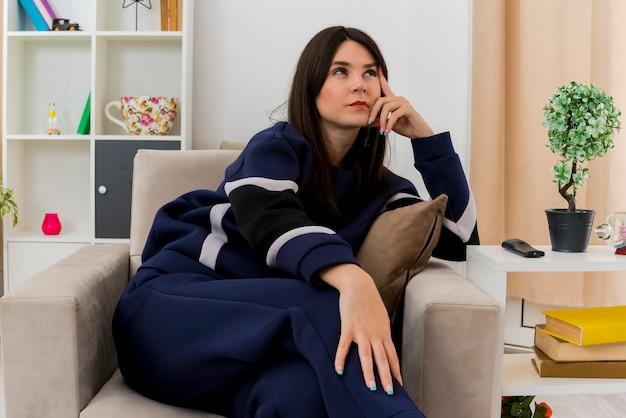 Rozważna młoda ładna kaukaska kobieta siedząca ze skrzyżowanymi nogami na fotelu w zaprojektowanym salonie patrząc z boku dotykając głowy palcem kładąc dłoń na nodze