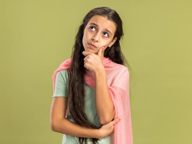 Rozważna Nastolatka Nosząca Szal, Patrząca W Górę, Trzymająca Rękę Na Brodzie Odizolowana Na Oliwkowozielonej ścianie Z Miejscem Na Kopię Premium Zdjęcia