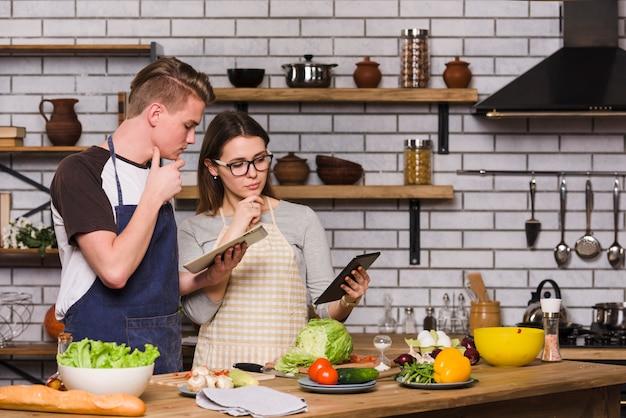 Rozważna para z pastylkami w kuchni