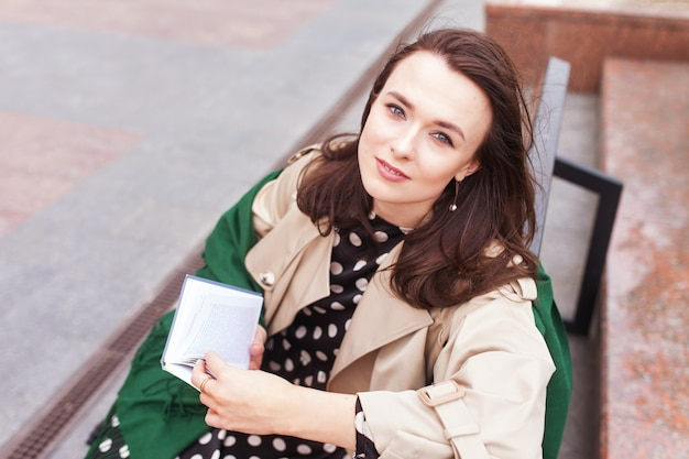 Rozważna piękna dziewczyna z książką w parku miejskim. piękna młoda kobieta. skopiuj miejsce