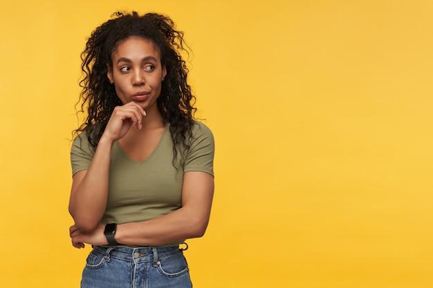 Rozważna piękna młoda kobieta w zwykłych ubraniach trzyma ręce złożone i myśli odizolowane nad żółtą ścianą