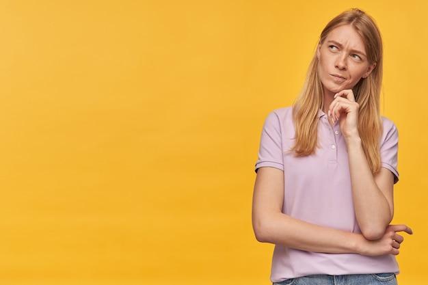 Rozważna, skoncentrowana kobieta z piegami w lawendowej koszulce, myśląca i odwracająca wzrok w pustą przestrzeń na żółto