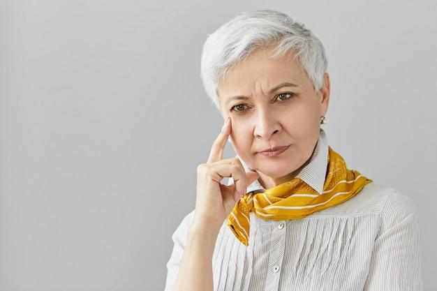 Rozważna, skoncentrowana starsza kobieta o siwych włosach pixie, mająca problemy z pamięcią, próbująca sobie coś przypomnieć, dotykająca twarzy. poważna dojrzała pani pozuje z zamyślonym spojrzeniem