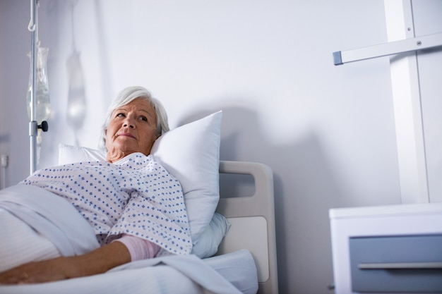 Rozważna starsza kobieta kłama na łóżku