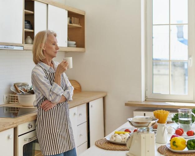 Rozważna starsza kobieta zaczyna nowy dzień z kawą, stojąc w kuchni w domu