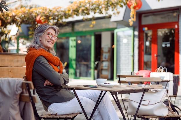 Rozważna starsza pani ze skrzyżowanymi rękami siedzi przy stole na tarasie kawiarni na świeżym powietrzu