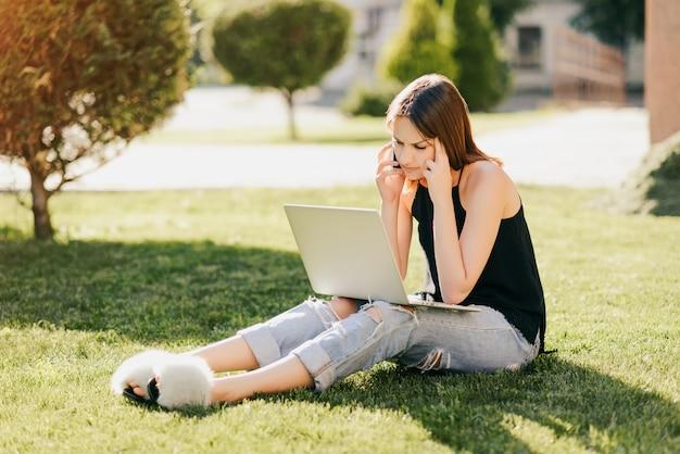Rozważna stylowa dziewczyna ma rozmowę telefoniczną, podczas gdy patrzejący ekran laptopu, siedzi na trawie w parku. ubrani w modne ciuchy. studia koncepcji.