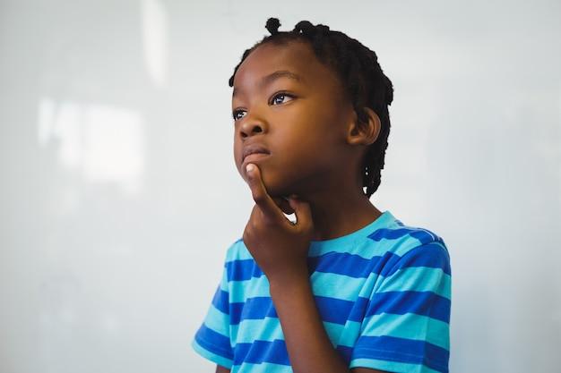 Rozważna uczniowska pozycja z ręką na podbródku w sala lekcyjnej