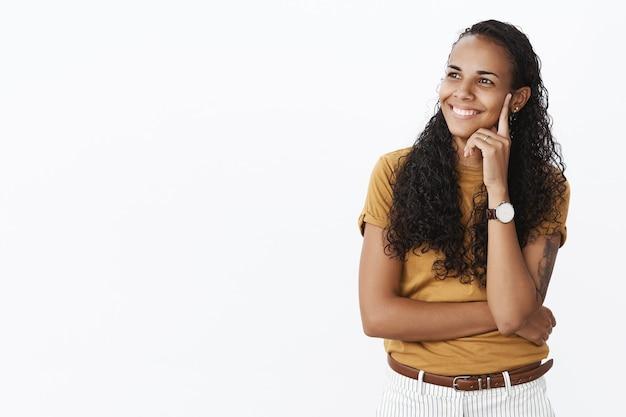 Rozważna, uśmiechnięta dziewczyna afroamerykanka, która patrzy w lewo z nadzieją