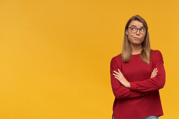 Rozważna wątpiąca blondynka. zaciągnięte usta. patrząc w lewy górny róg, stojąc z ręką złożoną po prawej stronie na białym tle. ubrany w czerwony sweter i okulary