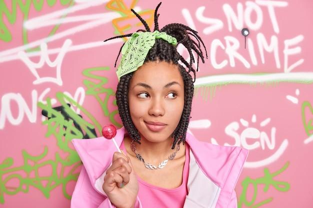 Rozważna, zamyślona nastolatka odwraca wzrok, trzyma słodkiego lizaka ubranego w modne ciuchy i czeka na pozę przyjaciół na tle kolorowej ściany z graffiti