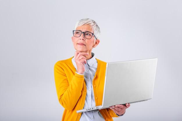 Rozważna zmieszana dojrzała kobieta zaniepokojona myśleniem o problemie online, patrząc na laptopa, sfrustrowana zmartwiona starsza kobieta w średnim wieku czytająca złe wiadomości e-mail, cierpiąca na utratę pamięci