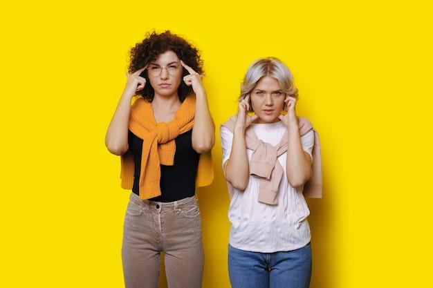 Rozważne kaukaskie kobiety z kręconymi włosami pozują na żółtej ścianie, dotykając jej głowy
