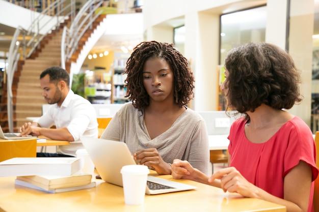 Rozważne kobiety używa laptop przy biblioteką