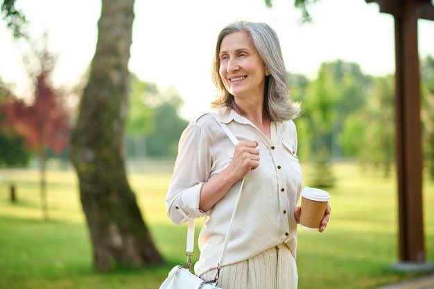 Rozważnie uśmiechnięta dorosła kobieta z kawą