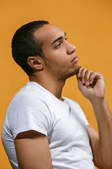 Rozważny afroamerykański mężczyzna patrzy w zamyśleniu na pomarańczę