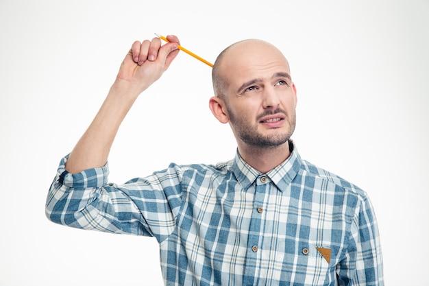 Rozważny, atrakcyjny młody mężczyzna drapiący się po głowie za pomocą zarobacza na białej ścianie