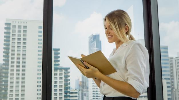 Rozważny bizneswoman pisze w notatniku w biurze