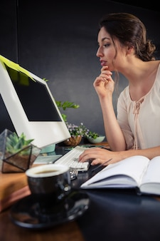 Rozważny bizneswoman używa jej komputer