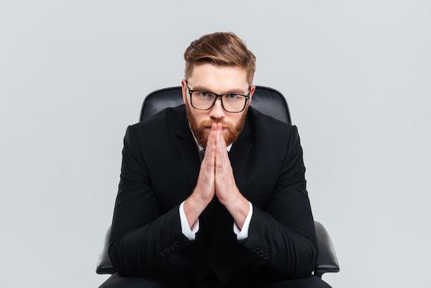 Rozważny brodaty biznesmen w okularach i czarnym garniturze siedzący na fotelu