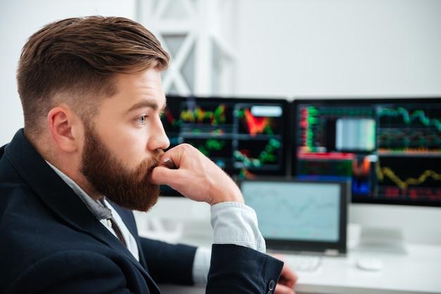 Rozważny brodaty młody biznesmen pracujący i myślący w miejscu pracy w biurze
