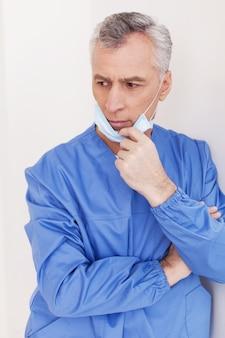 Rozważny chirurg. przygnębiony starszy lekarz z siwymi włosami zdejmuje maskę chirurgiczną, opierając się o ścianę
