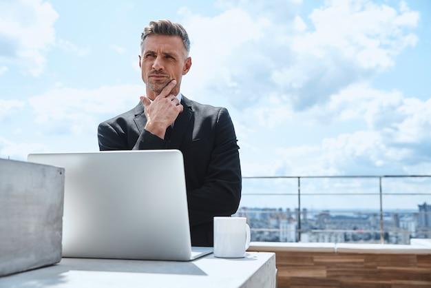 Rozważny dojrzały mężczyzna pracujący na laptopie i odwracający wzrok, stojąc na tarasie na dachu