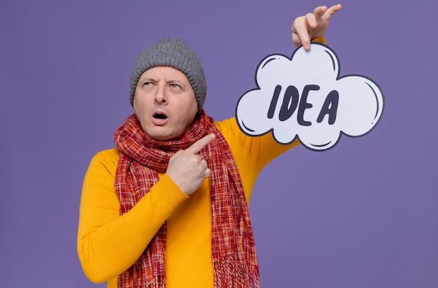 Rozważny dorosły mężczyzna w czapce zimowej i szaliku na szyi, trzymający i wskazujący na bańkę pomysłów
