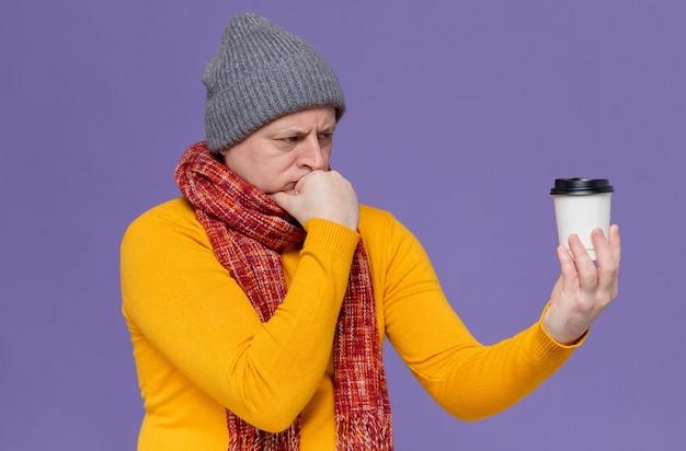 Rozważny dorosły mężczyzna w czapce zimowej i szaliku na szyi, trzymający papierowy kubek i patrzący na niego