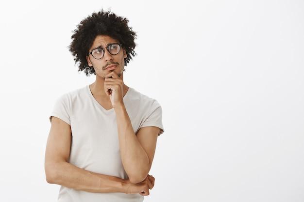 Rozważny, inteligentny człowiek w okularach, zakładający założenie, rozmyślający. człowiek myśli i patrząc w prawym górnym rogu puste miejsce na twoje logo