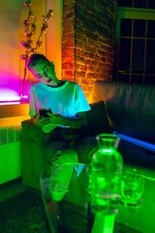 Rozważny. kinowy portret stylowej kobiety w oświetlonym neonem wnętrzu. stonowane jak efekty kinowe, jasne neonowane kolory. kaukaski model za pomocą smartfona w kolorowe światła w pomieszczeniu. kultura młodzieżowa.