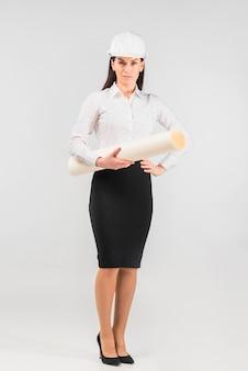 Rozważny kobieta inżynier w hełmie z whatman papierem
