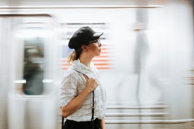 Rozważny kobiety czekanie dla pociągu przy metro platformą