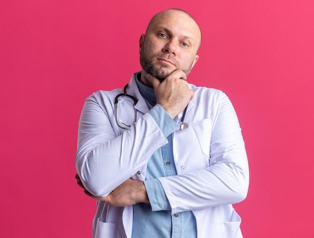 Rozważny lekarz w średnim wieku, ubrany w szatę medyczną i stetoskop, trzymający rękę na brodzie