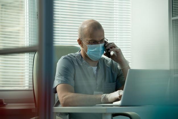 Rozważny łysy lekarz w peelingach siedzący przy biurku i korzystający z laptopa podczas omawiania danych online z kolegą przez telefon
