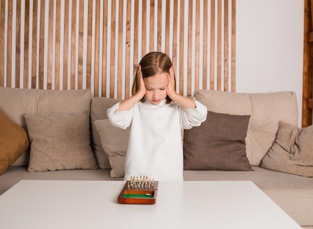 Rozważny mały szachista w białym swetrze siedzi na kanapie i gra w szachy
