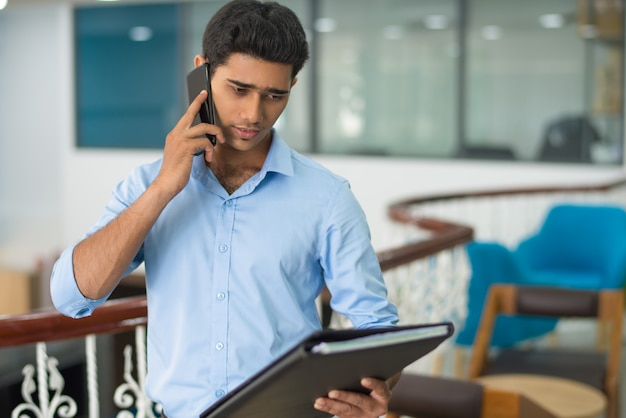 Rozważny mężczyzna dyskutuje dane podczas gdy opowiadający na telefonie komórkowym