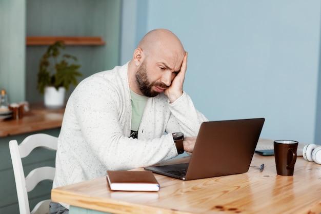 Rozważny mężczyzna pisze na laptopie, pracuje w domu, pracuje online, koronawirusa