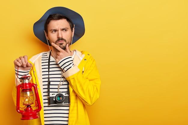 Rozważny mężczyzna trzyma podbródek, myśli o podróży lub wyprawie, trzyma małą lampkę gazową, ubrany w płaszcz przeciwdeszczowy, nakrycie głowy, używa aparatu do robienia zdjęć, odizolowany na żółtej ścianie