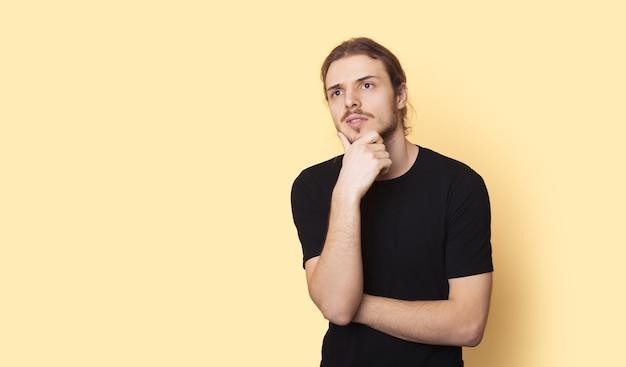 Rozważny mężczyzna z brodą i długimi włosami reklamuje coś na żółtej ścianie z wolnym miejscem