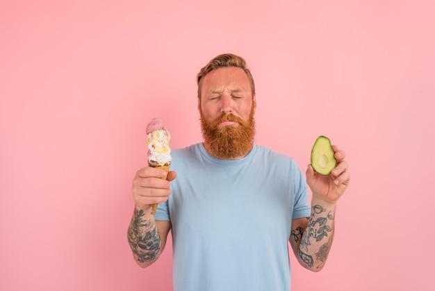 Rozważny mężczyzna z brodą i tatuażami jest niezdecydowany, czy zjeść lody, czy awokado