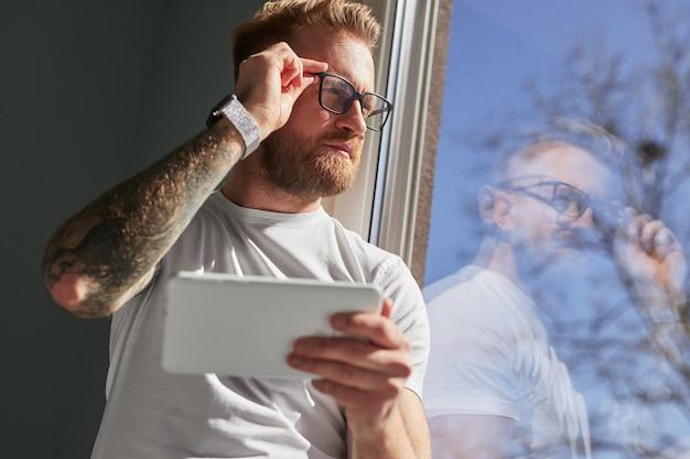 Rozważny mężczyzna z tabletem patrzącym w okno