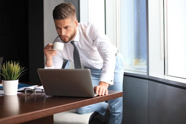 Rozważny młody biznesowy mężczyzna używa komputera i pije kawę podczas pracy w biurze.