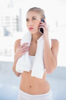 Rozważny młody blondynka model dzwoni z jej telefonem komórkowym