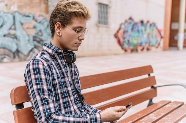 Rozważny młody człowiek ogląda wideo online na telefonie