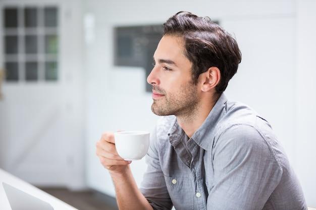 Rozważny młody człowiek trzyma filiżankę kawy